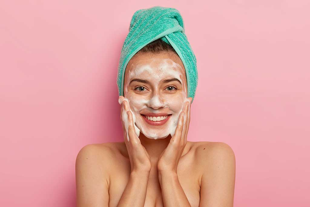 Positive Young Female Has Toothy Smile Has Perfect Teeth Pats Skin With Liquid Sanitary Soap Washes With Foaming Gel Wakes Up In Morning For Having Beauty Routine